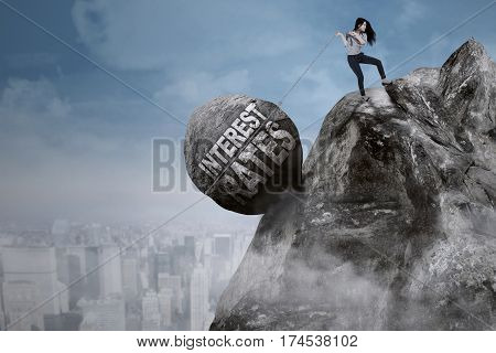 Beautiful businesswoman pulls big rock with text of interest rates on top of a cliff