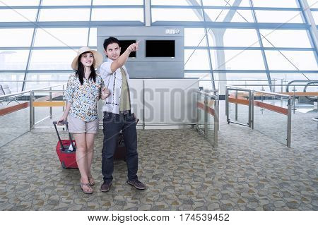 Two happy couple standing in the airport terminal while looking at something and carrying their bags