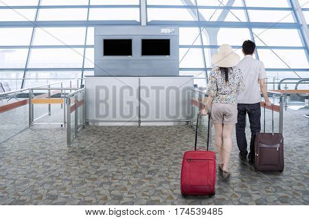 Rear view of two young couple walking in the airport terminal while carrying their luggage