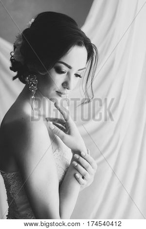 Black and white portrait of a beautiful bride. Bride waiting for the groom. White background. Eyes downcast. The big silver earrings. Female portrait in bridal gown for marriage. Cute lady indoors