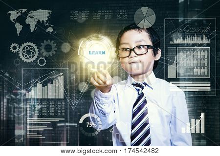 Image of little boy wearing glasses and touching a button with word learn on the touch screen