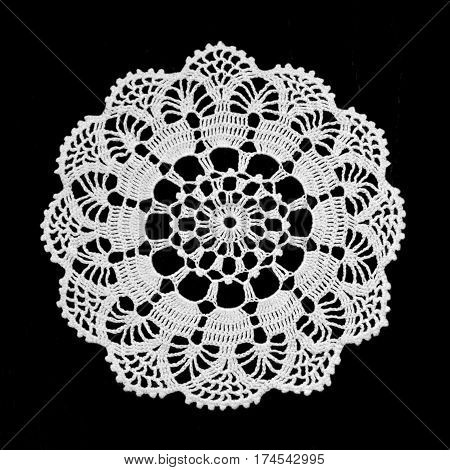 Handmade lace doily isolated on black background