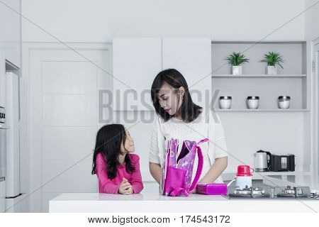 Beautiful mother and her daughter packing healthy lunch and preparing school bag in the kitchen