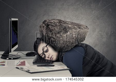 Businesswoman feels tired with heavy stone over her head while sleeps on the keyboard