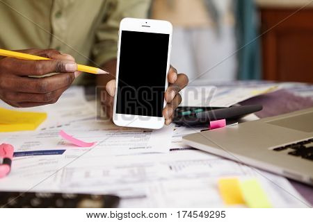 Close Up Shot Of Dark-skinned Man's Hands Holding Blank Screen Cell Phone And Pencil, Showing Someth