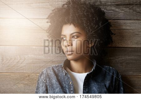 Headshot Of Fashionable Young Dark-skinned Woman With Afro Haircut Dressed In Denim Jacket Over Whit