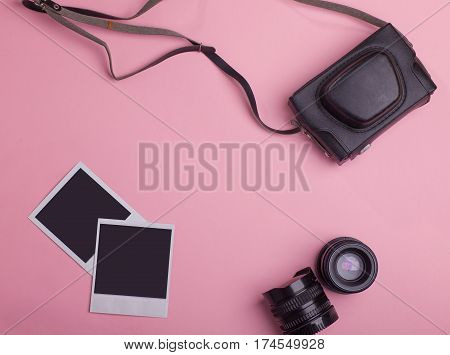 blank photo frames vintage photo camera bag lenses around blank copy space isolated on pink background flat lay