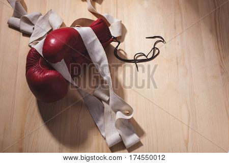 boxing-glove with white old hand-wrap on wooden surface with right copy space