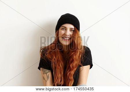 Isolated Studio Portrait Of Fashionable Female Model With Gorgeous Long Ginger Hair Looking And Smil