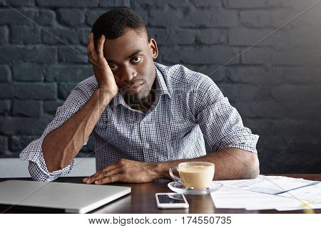 Tired And Unhappy Young Manager With Headache Having Exhausted And Overworked Look, Leaning On His E