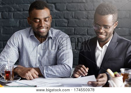 Two Successful Business Partners Having Positive Conversation, Discussing Provisions Of Contract, Si