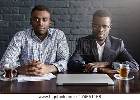 Indoor Shot Of Two Successful Businessmen Having Meeting In Modern Office Interior, Sitting At Table