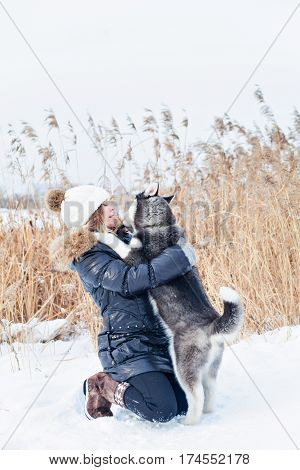 Smiling young woman hugging a small husky pup. Vertical outdoors shot.