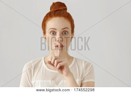 Portrait Of Emotional Redhead Girl With Freckles And Hair Bun Holding Index Finger At Her Lips, Sayi