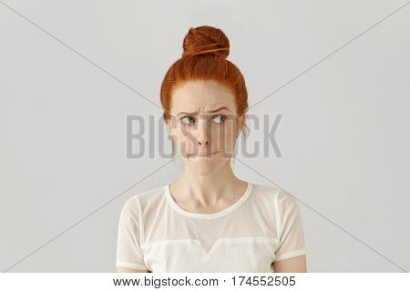 Studio Isolated Shot Of Doubting Confused Cute Young Redhead Freckled Female Looking Sideways, Pursu