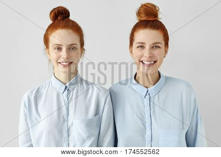 Two Young Redhead Caucasian Females Looking Alike Wearing Same Formal Light-blue Shirts, Looking At