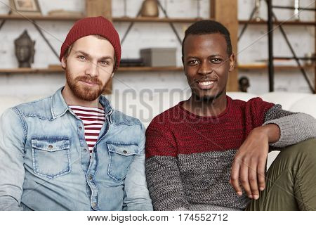 International Friendship Concept. Indoor Shot Of Two Stylish Young Men Having Rest In Modern Cafe In