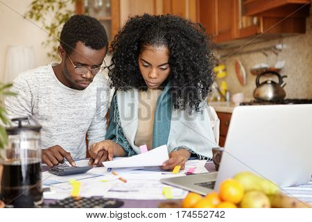 Young African-american Couple Managing Finances Together At Home: Man Wearing Glasses Making Calcula