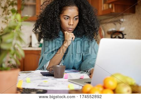 Serious Young African-american Female In Warm Wrap Working Through Finances At Night, Sitting At Kit