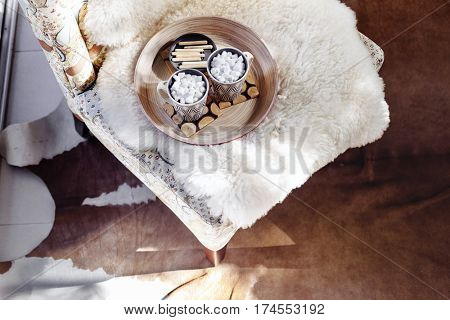Details of nordic interior. Wooden tray served with two cups of cocoa with marshmallows on armchair with sheep fur cover, cow skin rug on floor, top view from above. Winter morning in log cabin.