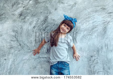 Fashion child wearing blank gray t-shirt and jeans posing against rough concrete wall, minimalist street fashion kids style
