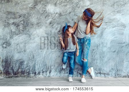 Young beautiful mom with her daughter wearing blank gray t-shirt and jeans posing against rough concrete wall, minimalist street fashion style, family same look, clothing for parent and child.