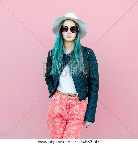 Fashionable young blogger woman with blue hair wearing casual style outfit with black jacket white hat pink jeans and sunglasses posing near the wall.