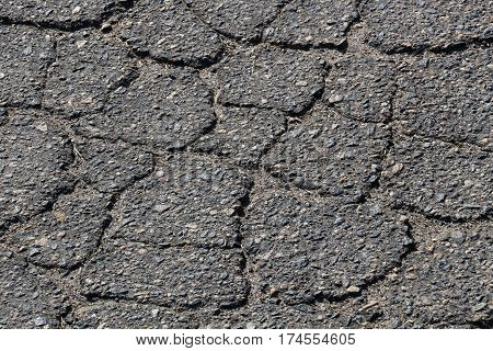 Closeup of crumbling asphalt roadway, breaking up into irregular polygonal pieces due to age, traffic and weather.