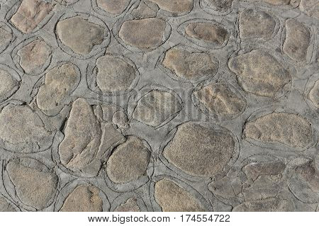 Path or patio surface constructed of flat rocks and cement, with incised pattern around rocks.