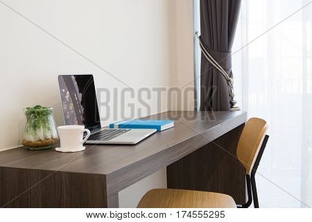 office table with blank screen laptop white coffee cup modern chair and garden plant garden on cement wall background view from front office table concept of business lifestyle.