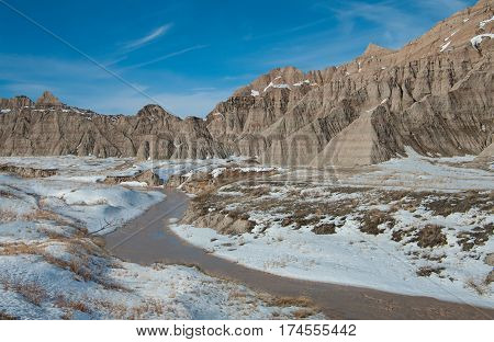 Flowing Arroyo:  A stream bed that is usually dry fills with melting snow on a winter day in Badlands National Park.