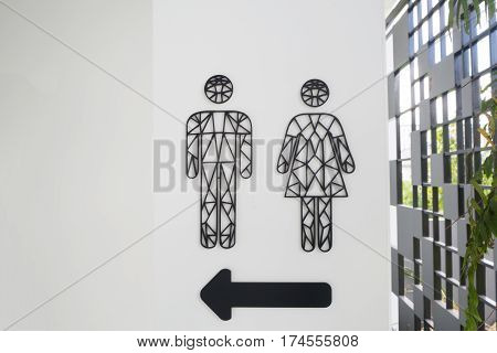 male and female toilet sign with arrow sign on cement wall background.