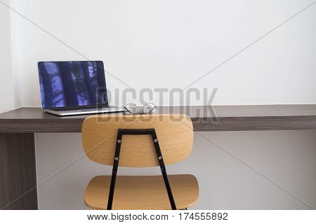 office table white laptop modern chair and modern eyeglasses. concept of business lifestyle. view from front office table.