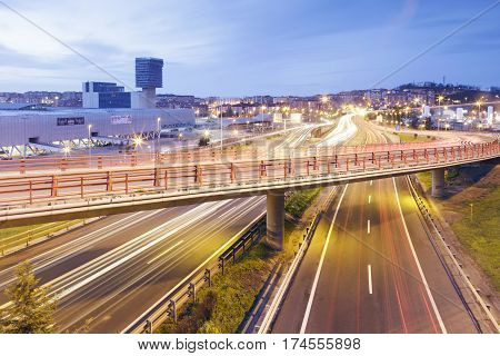 BARAKALDO SPAIN - MARCH 5 2017: Car light trails in the highway near the city of Barakaldo and the Bilbao Exhibition Center (BEC). Long exposure shot at sunset.