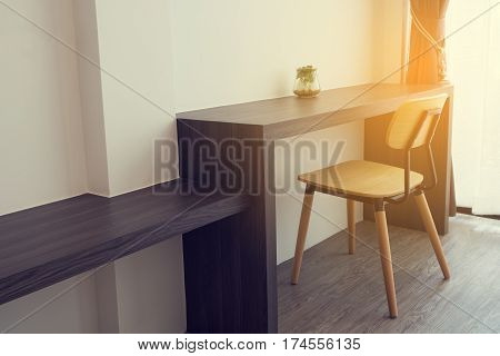 office table with garden plant on glass vase and modern chair at working room. side view office table.