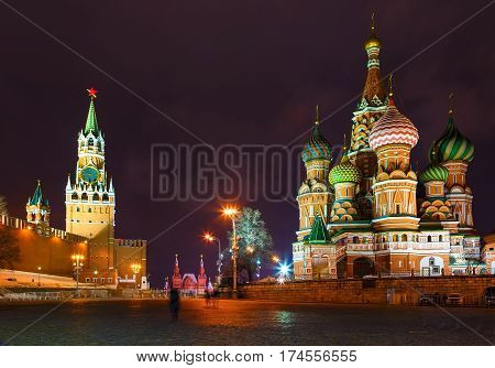 Saint Basil's Cathedral at the Red Square in Moscow by a winter night illuminated by streetlight with Kremlin wall and cloudy sky as a background and pavement of rectangular stones as a foreground.
