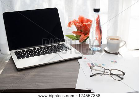Office table with blank screen on laptop and beautiful flower bottle of drink coffee cup business report paper ,View from fron office table Business time concept