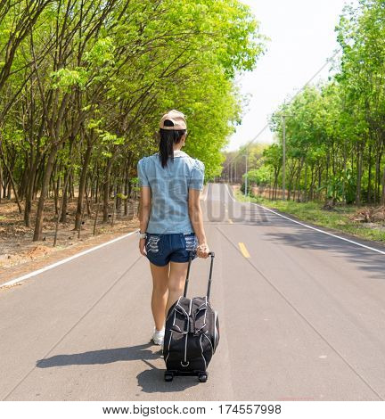 Woman walking on the road Travel, dragging a suitcase.