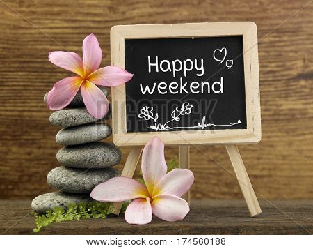 stack of pebbles and mini blackboard with text happy weekend
