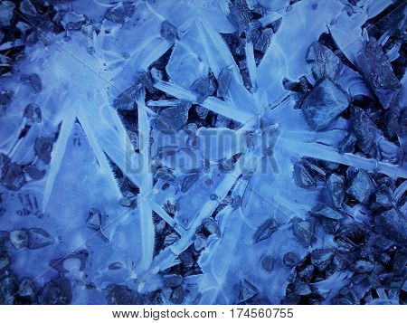 Sprawling ice over a rocky ground in a blue hue.