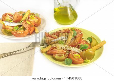 Plates of tomato and anchovies salad on a white background with a place for text