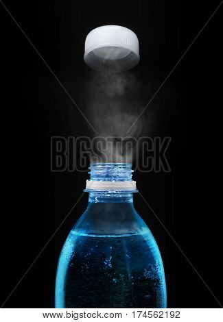 Top of open plastic bottle with carbonated mineral water in the dark