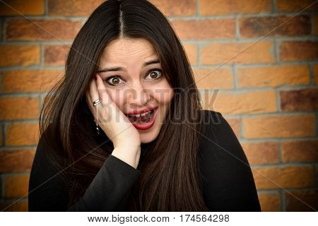 Portrait of a surprised and frightened beautiful young woman in front of the brick wall