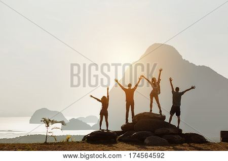 Group of four people stands on the top of mountain in winner pose. Team or teamwork success concept. Space for text
