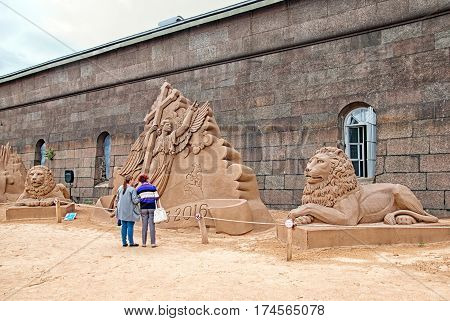 SAINT-PETERSBURG, RUSSIA - AUGUST 15, 2016: People look at the sand sculptures on The Sand Sculpture Festival near The Peter and Paul Fortress Wall