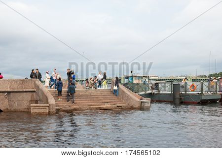 SAINT-PETERSBURG, RUSSIA - AUGUST 15, 2016: People take pictures of the city from The Commandant Pier, part of The Peter and Paul Fortress. On the background is The Trinity Bridge