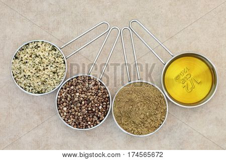 Health food with hulled hemp seed, dried seeds, powder and cooking oil in measuring scoops on natural hemp paper background. Left to right.