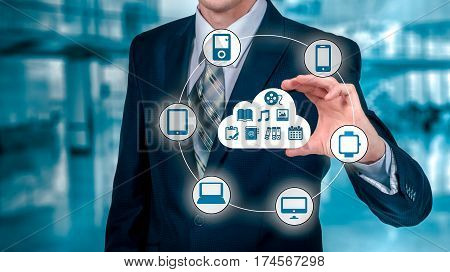 Businessman touching a cloud connected to many objects on a virtual screen, concept about internet of things.