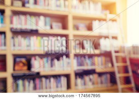 blurred bookshelf in library room for your background design - vintage color styles.