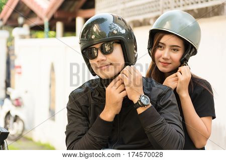 Young Adult Asian Couple Male and Female Biker or Motorcyclist Wearing Safe Helmet before Travel on Motorcycle as Accident Prevention or Safety Riding Concept.